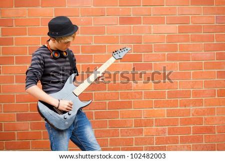 teen boy playing guitar outdoors - stock photo