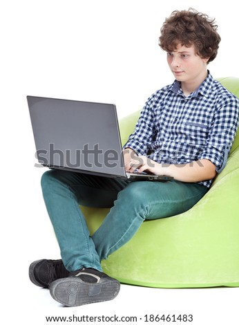 Teen boy playing on notebook - stock photo