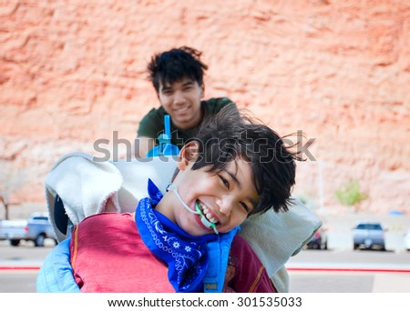 Teen boy pushing happy disabled biracial little  brother in wheelchair, smiling and laughing, outdoors. cerebral palsy - stock photo