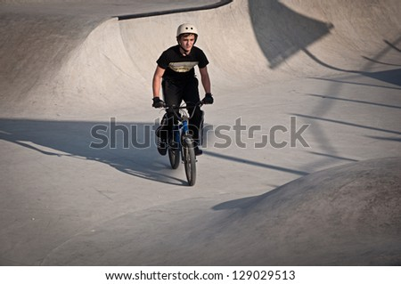 Teen boy rides a bicycle in the bike park . - stock photo