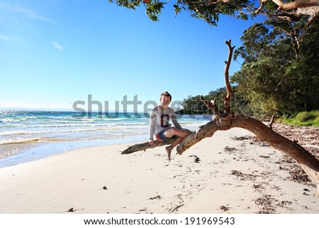 Teen boy sitting on a gum tree outstretched branch enjoying a vacation on a glorious day at the beach in NSW Australia - stock photo