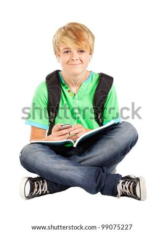 teen boy sitting on floor and listening music - stock photo