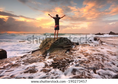 Teen boy stands on a rock among turbulent ocean seas at sunrise.  Worship, praise, zest, adventure, solitude, finding peace among lifes turbulent times.  Overcoming adversity.  Motion in water - stock photo