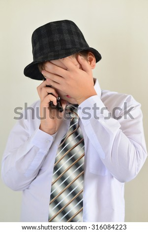 Teen boy talking on cell phone on a light background - stock photo