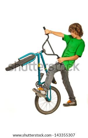 Teen boy trying stunt on bike isolated on white background - stock photo