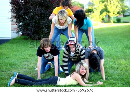 teen boys and girls making a pyramid - stock photo
