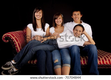 Teen children from a multicultural American family of six in a seated studio portrait with a black background. - stock photo