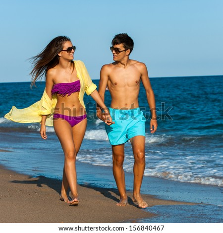 Teen couple in swim wear holding hands at seaside. - stock photo
