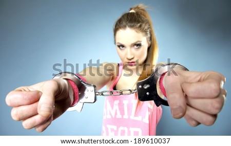 teen crime - teenager girl in handcuffs studio shot blue background - stock photo