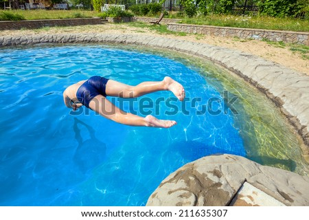 Teen dives into a swimming pool with springboard - stock photo