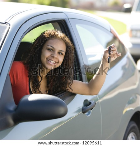 Teen driver inside car with keys smiles - stock photo