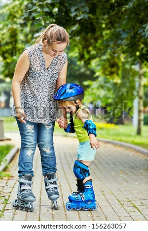 Teen girl and little boy in roller protective equipment stand holding hands on walkway in park - stock photo