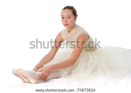 teen girl ballet dancer sitting in a tutu in points on a white background - stock photo