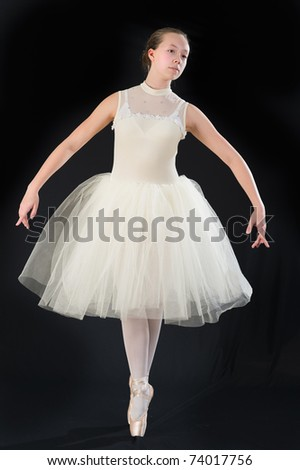 teen girl ballet dancer standing in a tutu in points on a black background - stock photo