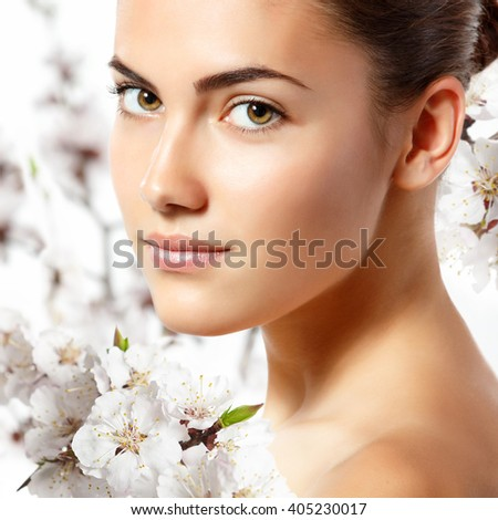 teen girl beauty portrait looking at camera over blooming tree with flowers. Spring, youth, freshness, beauty, skincare and health-care concept. - stock photo