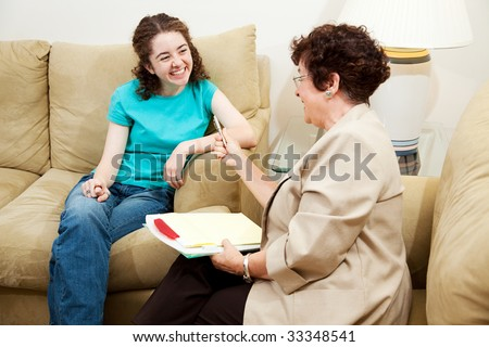 Teen girl being interviewed by a middle aged woman.  Could be counselor or job application. - stock photo