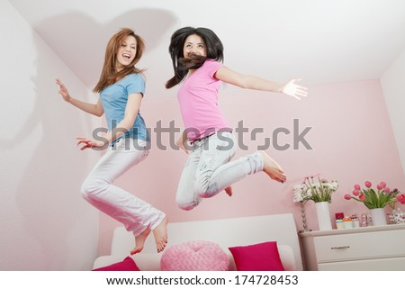 Teen girl birthday party : two happy teens jumping on the bed in her room. - stock photo