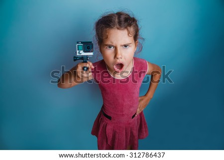 Teen girl child seven years, European appearance brunette holding action camera and opened her mouth on a gray background, anger, scream - stock photo
