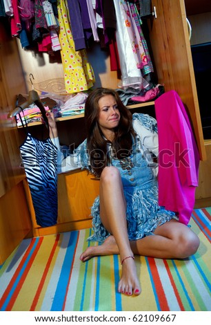 teen girl choosing clothes in front of full closet - stock photo