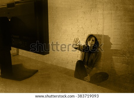 teen girl cyber abused suffering internet cyberbullying scared and desperate in fear face expression sitting on the floor in front of computer monitor in  bullying social problem edgy grunge lighting - stock photo