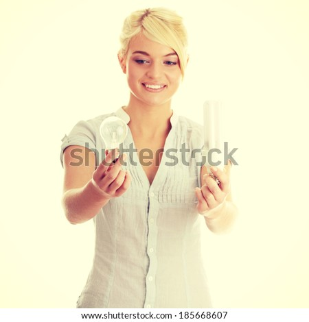 Teen girl environmentalist comparing one compact fluorescent light bulb to incandescent light bulb  - stock photo