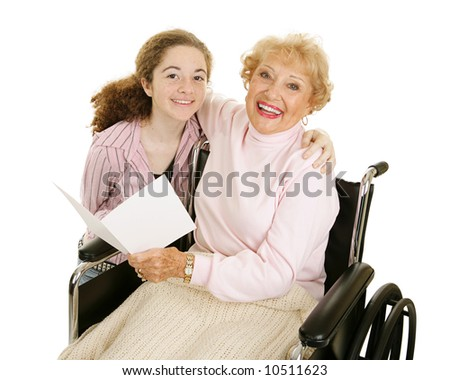 Teen girl gives greeting card to her grandmother for mothers day or other holiday. - stock photo