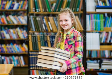 Teen girl holding pile books in the library - stock photo
