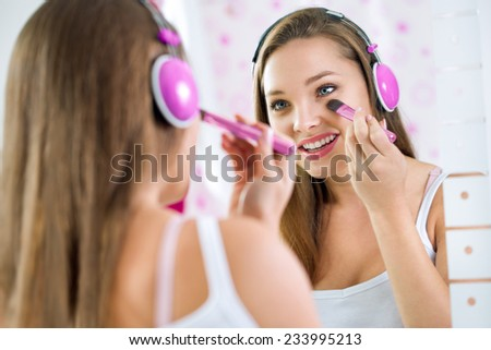 Teen girl in bathroom makeup and listening to music - stock photo