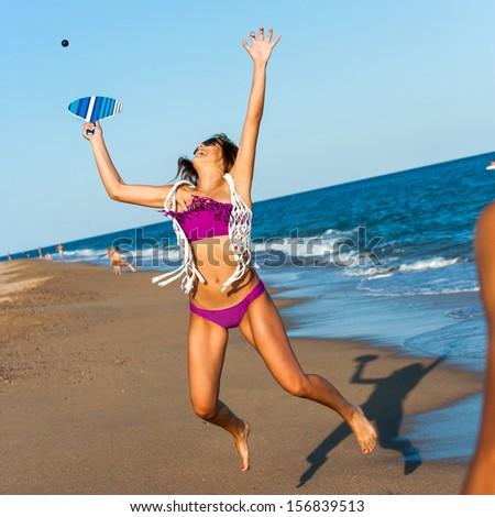 Teen girl jumping at beach tennis ball outdoors. - stock photo