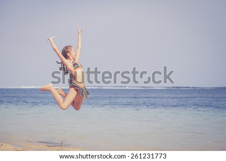 teen girl  jumping on the beach at blue sea shore in summer vacation at the day time - stock photo