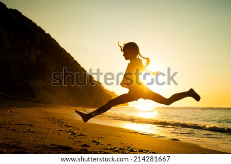 teen girl jumping on the beach at the day time - stock photo