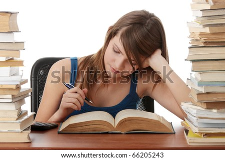 Teen girl learning at the desk, with lot of books around, isolated on white - stock photo