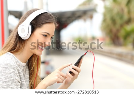 Teen girl listening to the music with headphones in a train station while she is waiting  - stock photo