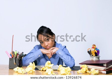 Teen girl looks bored as she sits at a desk surrounded by crumpled paper, pens, pencils, and folders. Horizontally framed photograph - stock photo