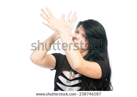 Teen girl making funny face using both hands - stock photo