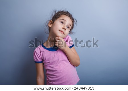 Teen girl of European appearance, brunette holds hand on chin looking away, daydreaming - stock photo