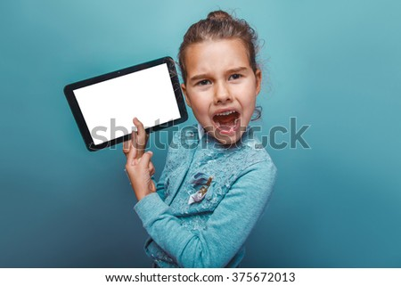 teen girl of  European appearance  seven  years in the hands holding the tablet opened her mouth on a gray background shouts - stock photo