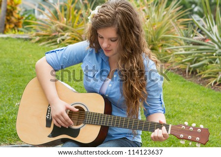 Teen girl playing the guitar outside in a tropical setting. - stock photo