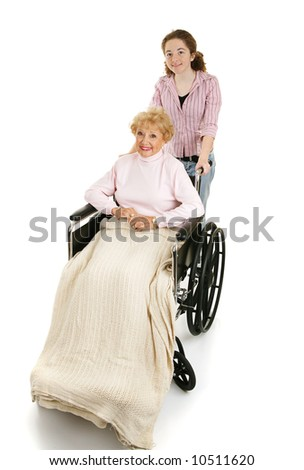 Teen girl pushing a disabled senior woman in a wheelchair.  Isolated on white. - stock photo