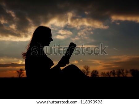 Teen girl reading book outdoors at sunset time - stock photo