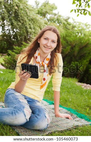 Teen girl reading electronic book outdoors - stock photo