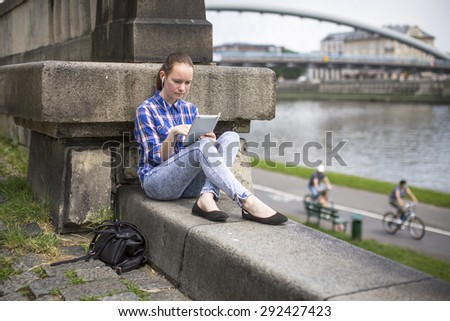 Teen girl sitting with the tablet outdoors in the city near the river. - stock photo