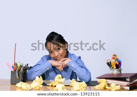 Teen girl smiling as she sits at a desk surrounded by crumpled paper, pens, pencils, and folders. Horizontally framed photograph - stock photo