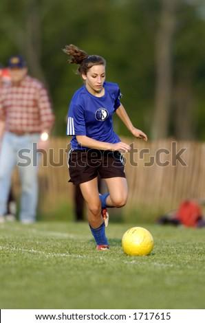 Teen Girl soccer player runs after yellow soccer ball - stock photo