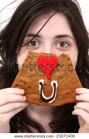 Teen girl spelling out Eye Love You with a cookie in front of face. - stock photo