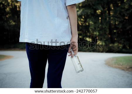 Teen girl standing at a fork in the road with a beer bottle - stock photo