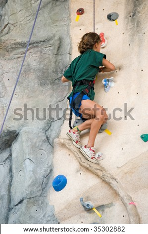 teen girl standing on a narrow ledge of an artificial rock climbing wall - stock photo
