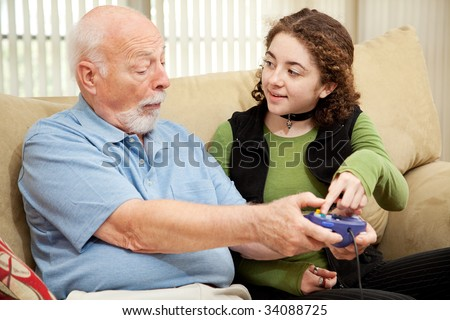 Teen girl teaching her grandfather how to play video games. - stock photo