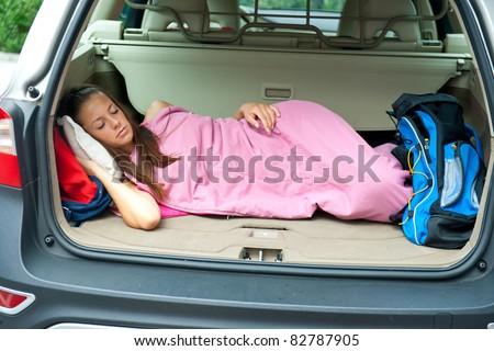 teen girl tourist resting in sleeping bag in her car - stock photo