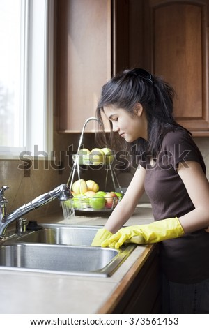 Teen girl washing dishes at kitchen sink - stock photo